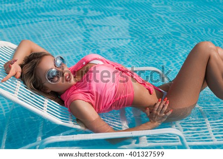 girl in swimwear in the pool, with glass