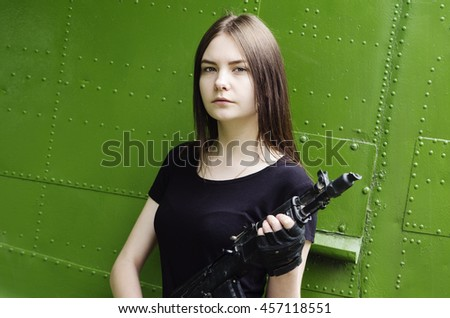Girl in the black T-shirt with a gun, posing against the backdrop of the fuselage military transport aircraft - stock photo