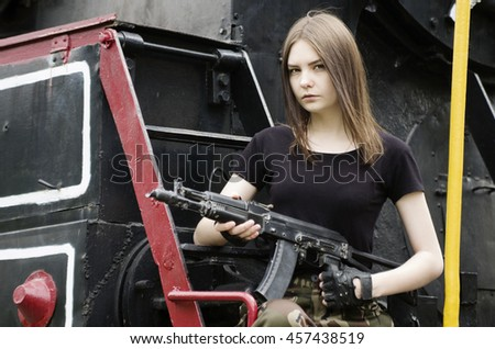 Girl in the black T-shirt with a gun, posing near a locomotive - stock photo