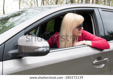 Girl in the car looks back - stock photo