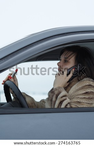 Girl in the car  talking on a cell phone and holding a lipstick in her hand