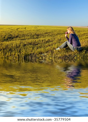 Girl in the field near the water smells a bunch of flowers - stock photo
