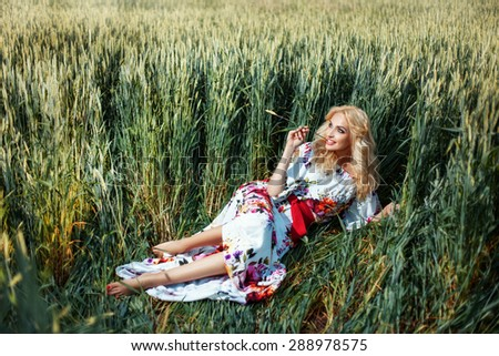 Girl in the field with ears of corn in his hand. She in a summer dress. She dreams of romance. - stock photo