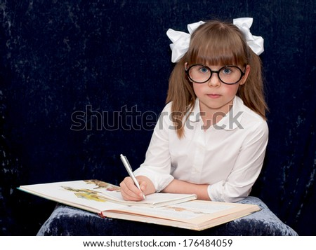 Girl in the glasses is doing her homework - stock photo