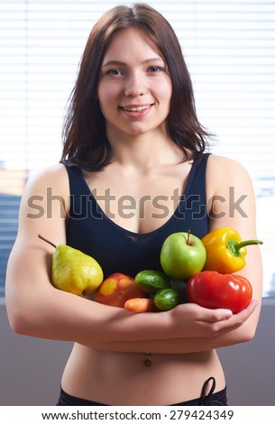 Girl in the gym holding a lot of vegetables