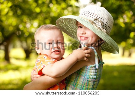 Girl in the hat keeps the arms of his younger brother