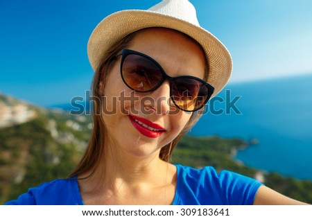 Girl in the hat making selfie by the smartphone on the background of sea coast,  Adriatic sea, Montenegro, Balkans