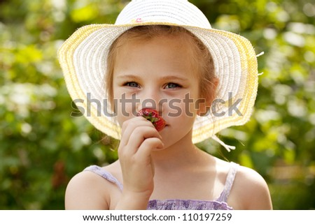Girl in the hat smells ripe fresh strawberries - stock photo