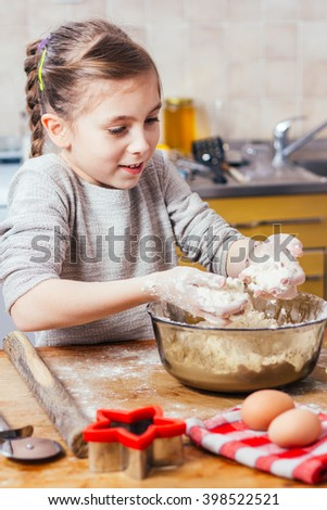 Girl in the kitchen playing with flour - stock photo