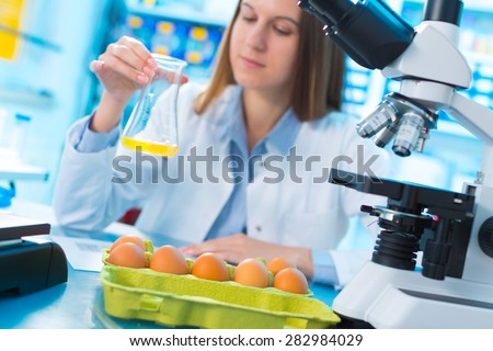 girl in the laboratory testing of food quality egg. Check the content of protein, fat, cholesterol and pathogens - stock photo