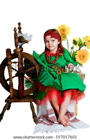 girl in the national Ukrainian costume sitting near the spinning wheel on the background of sunflowers - stock photo