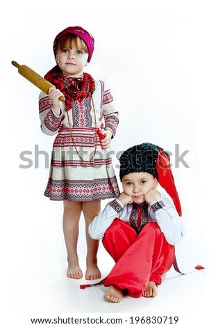 Girl in the national Ukrainian costume with embroidery and a rolling pin in her hand and a boy in fur hat Cossack sits brooding - stock photo