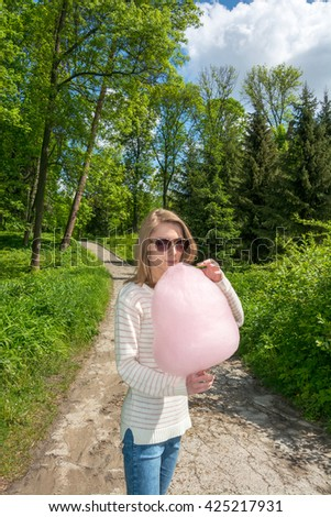 Girl in the park eating cotton candy - stock photo