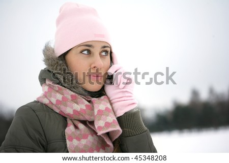 Girl in the park in winter on the phone and smiling - stock photo
