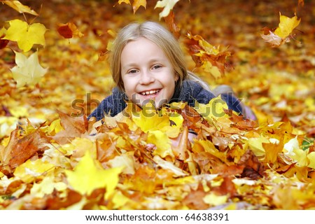 Girl in the park under falling autumn leaves - stock photo