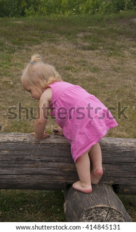 girl in the pink dress on the big log - stock photo