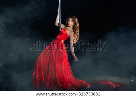 Girl in the red dress dances around a pole dancing night mist. See more images from this series.