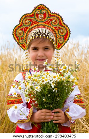 Girl in the Russian national sundress and a kokoshnik to stand in the field with a bouquet of camomiles