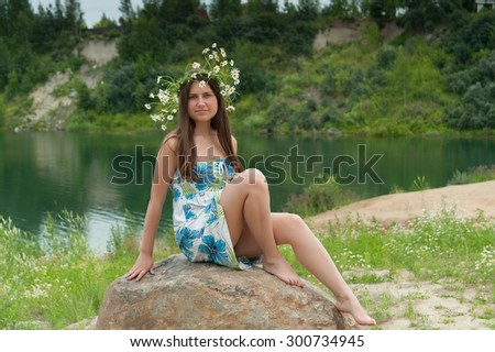 girl in the sundress with daisies on stone lake