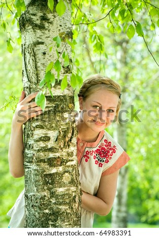 girl in traditional clothes near birch in summer - stock photo