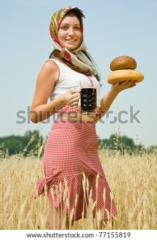 Girl in traditional clothes with bread and kvass at wheat field - stock photo