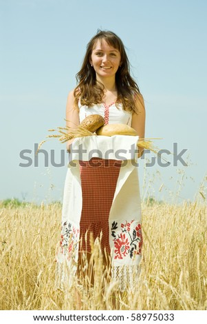 Girl in traditional clothes with bread  at wheat field - stock photo
