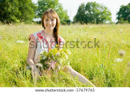 girl in traditional clothes with flowers  sitting  on meadow