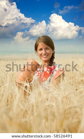 girl  in traditional clothes with jug at cereals field in summer - stock photo