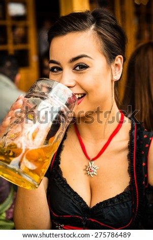 Girl in traditional Dirndl dress, interesting Asian and German multi-racial, is drinking beer and having fun at the Oktoberfest - stock photo