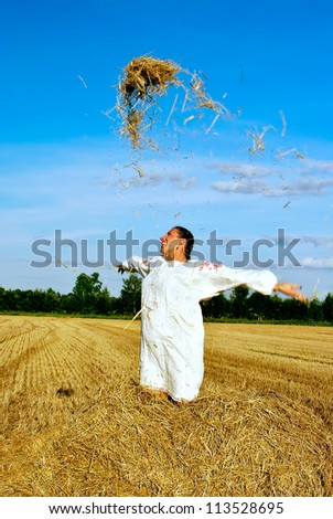girl in traditional Russian costume toss hay on a haystack - stock photo