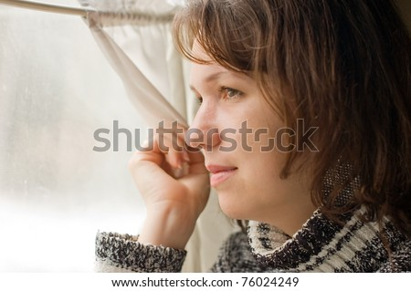 Girl in train looks out of window - stock photo