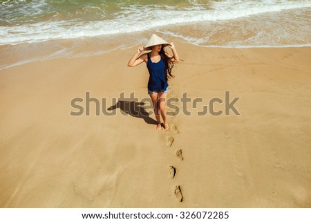 girl in tropics with vietnamese hat on the beach top view