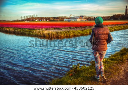 girl in tulip fields is back looking into the distance - stock photo