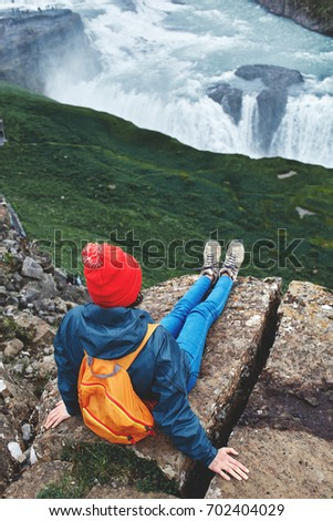 Girl in warm clothing, in red knitted hat and small orange backpack sits on the cliff on background of Gullfoss waterfall in Iceland. View from above