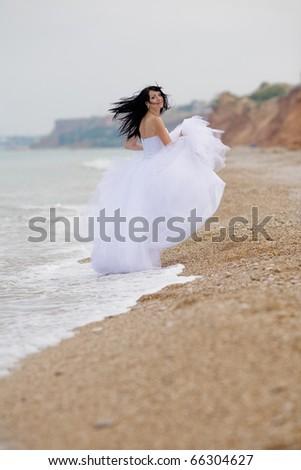 Girl in wedding dress running along the beach - stock photo