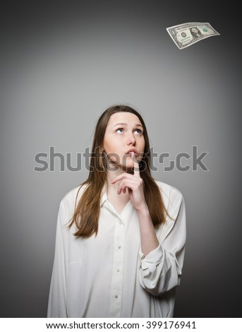 Girl in white and falling one dollar. First salary concept. - stock photo