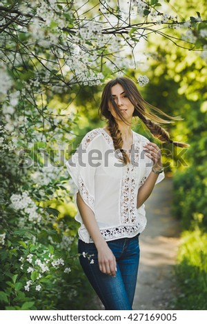 Girl in white blouse walking through the garden.