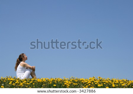 Girl in white clothes sitting in a flowering dandelion field. - stock photo