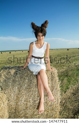 Girl in white dress and interesting hairstyle in countryside, summer shoot - stock photo