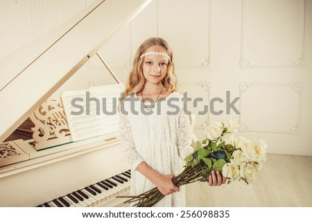Girl in white dress clothed is standing in front the piano. She is holding a roses in her hands. - stock photo