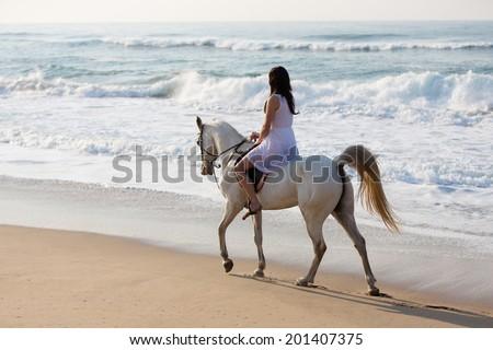 girl in white dress enjoying horse ride on the beach - stock photo