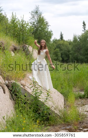 girl in white dress on a concrete wall - stock photo