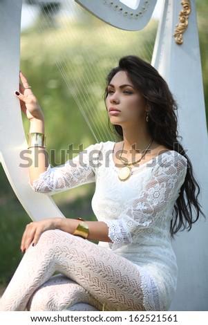 girl in white dress playing the harp white - stock photo
