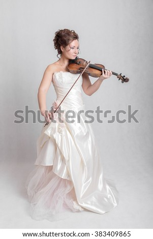 girl in white dress playing the violin - stock photo