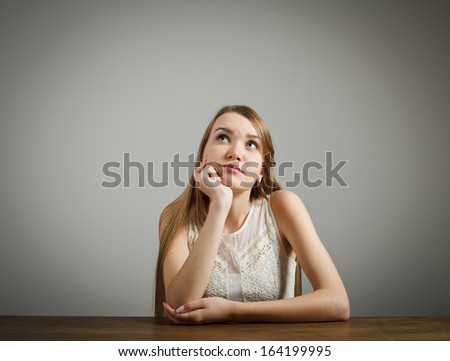Girl in white full of doubts and hesitation. Girl solving a problem. - stock photo