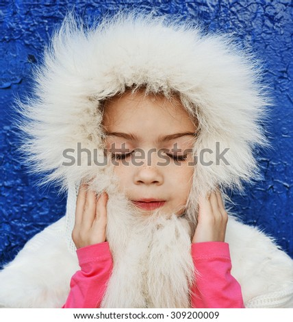 Girl in white fur on blue background - stock photo