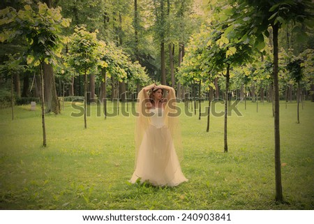 girl in white-golden gown in the summer park between young trees, instagram image style