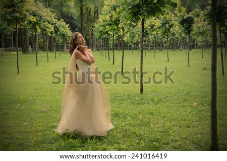 girl in white-golden gown in the summer park between young trees peers into sky, instagram image style