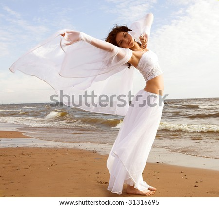 Girl in white gown dancing on the seashore