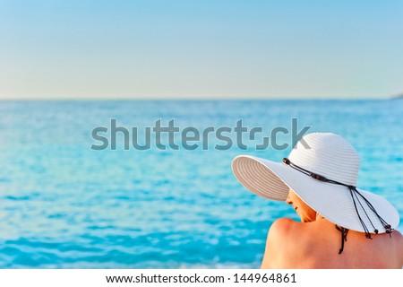 girl in white hat on the beach sunbathing - stock photo